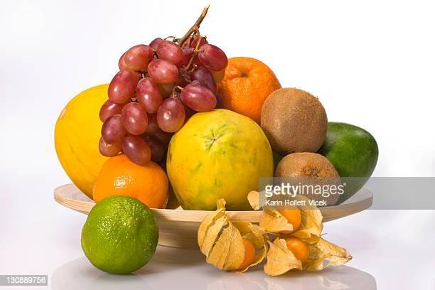 Exotic fruit on a wooden plate, melon, grapes, orange, lime, physalis, kiwis, mango, papaya
