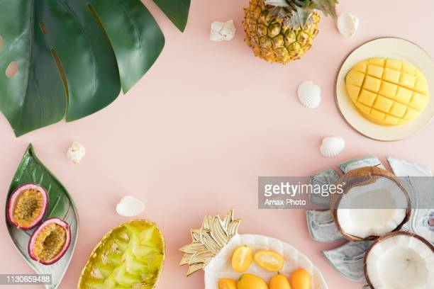 exotic fruits on pastel pink background - pineapple, mango, coconut, carambola, passion fruit. top view and flatlay - tropical fruit stock pictures, royalty-free photos & images
