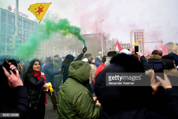 Expatriate Kurds burn colour bombs as they participate in celebrations marking the Kurdish new year or Newroz on March 17 2018 in Hanover Germany...