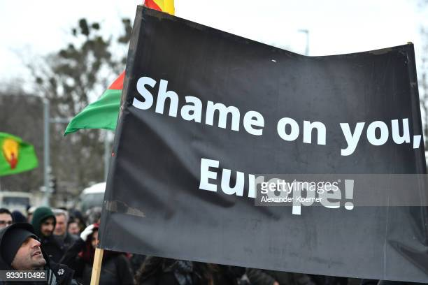 Expatriate Kurds hold a banner reading 'Shame on you Europe' and shout slogans against Turkish President Recep Tayyip Erdogan as they participate in...