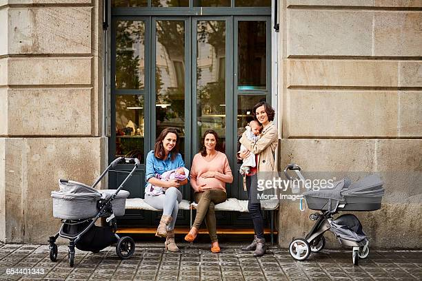 Expectant and friends with babies on sidewalk