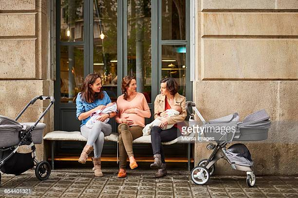 expectant and friends with babies sitting on bench - carriage stock pictures, royalty-free photos & images
