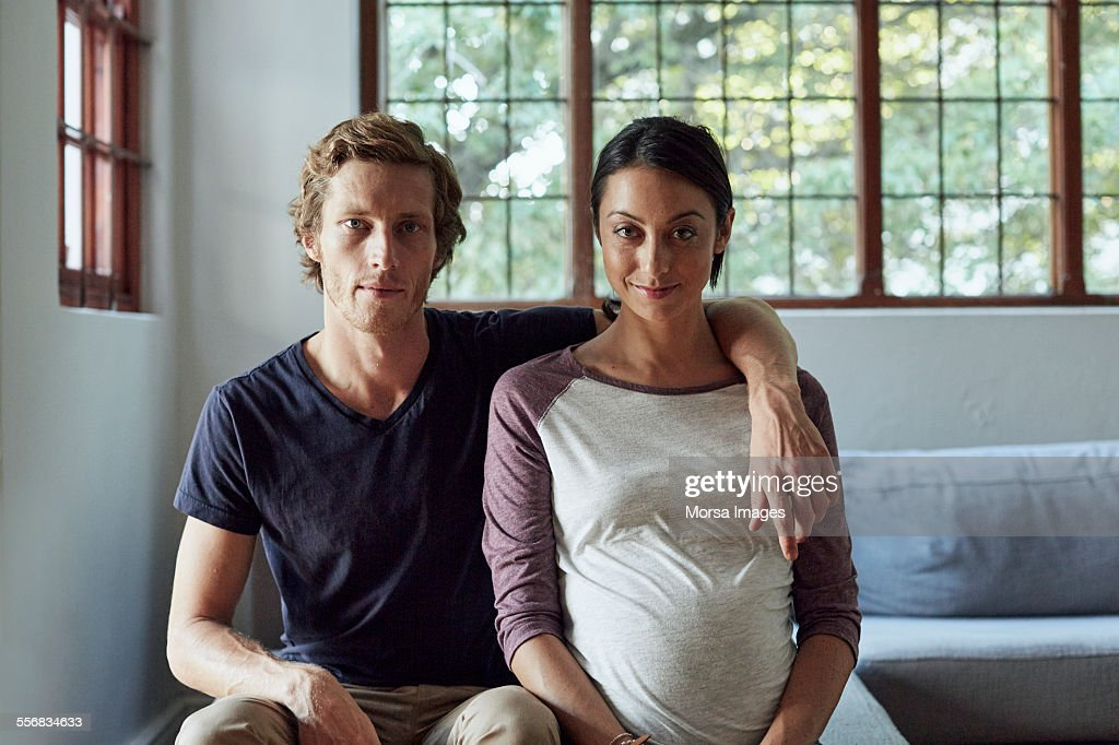 Expectant couple sitting on sofa at home : Stock Photo