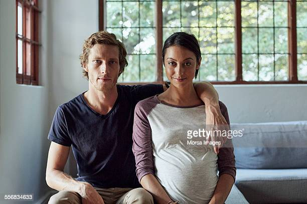 expectant couple sitting on sofa at home - mid volwassen mannen stockfoto's en -beelden
