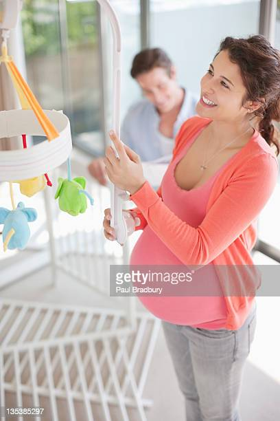 Expectant mother looking at crib mobile