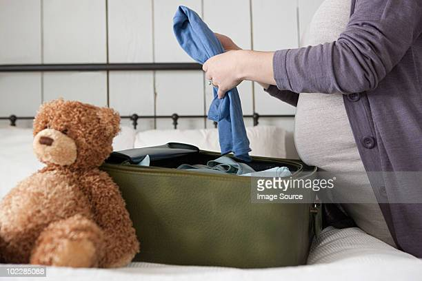 Expectant mother packing suitcase