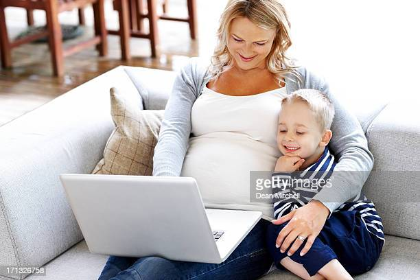 Expectant mother with her son using laptop - Indoors