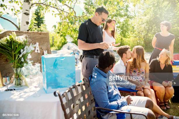 expectig couple kissing in the middle of baby shower outdoors. - baby shower stock photos and pictures