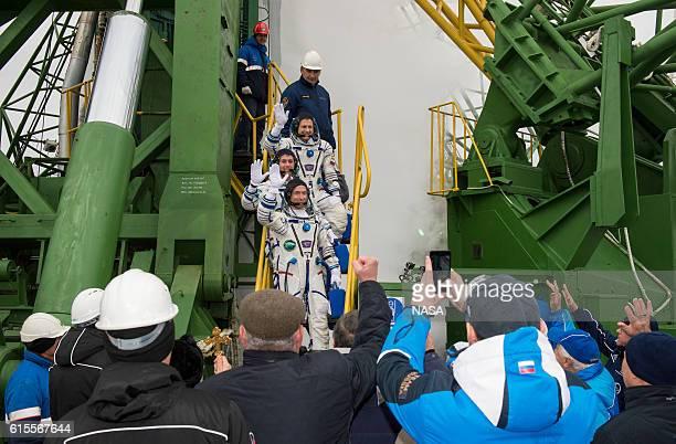 Expedition 49 flight engineer Andrey Borisenko of Roscosmos Shane Kimbrough of NASA and Soyuz commander Sergey Ryzhikov of Roscosmos wave farewell...