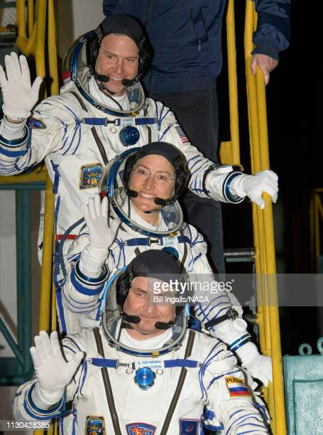 Expedition 59 crewmembers Nick Hague of NASA top Christina Koch of NASA center and Alexey Ovchinin of Roscosmos wave farewell prior to boarding the...