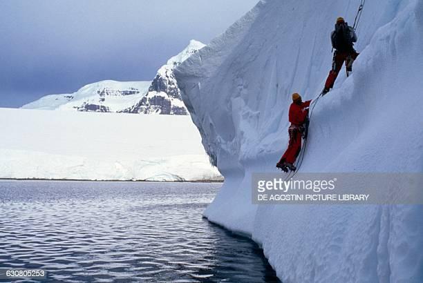Expedition members climbing up an iceberg Antarctica