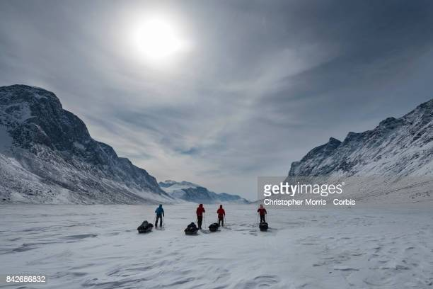 Expedition members cross the frozen landscape of the Weasel River, while towing sleds, during a ski traverse of Akshayuk Pass, in Auyuittuq National...