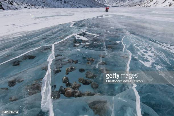 Expedition members cross the frozen Weasel River, with boulders suspended in the ice, during a ski traverse of Akshayuk Pass, in Auyuittuq National...