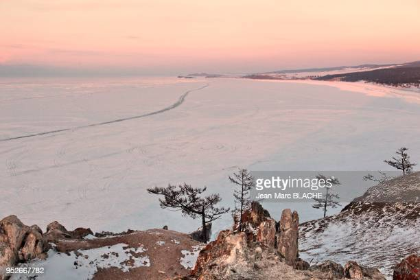 Expedition to Lake Baikal in Siberia Bakal Lake under ice in winter Rock of Shamans on Olkhon Island on March 7 2011 Landscape on sunset of Baikal...