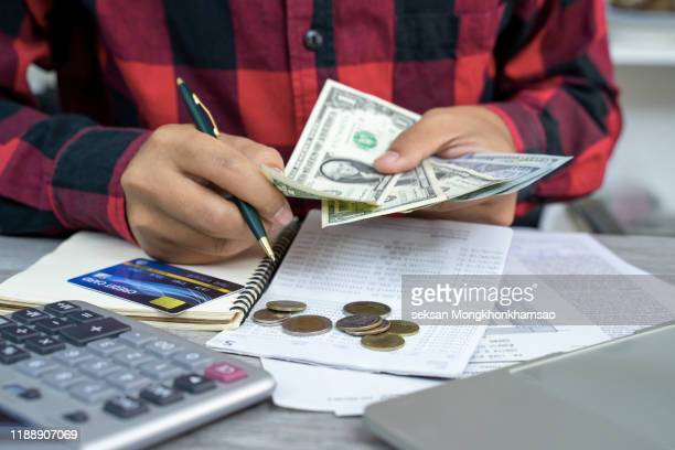 expense and budget concept, woman hand holding euro banknote money with list of expense in small notepad and calculator on wooden table. - devolver - fotografias e filmes do acervo