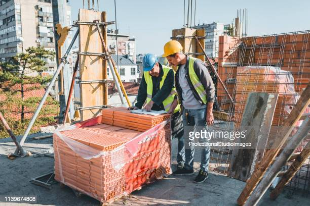 experienced construction worker is explaining building project to his coworker - construction material stock pictures, royalty-free photos & images