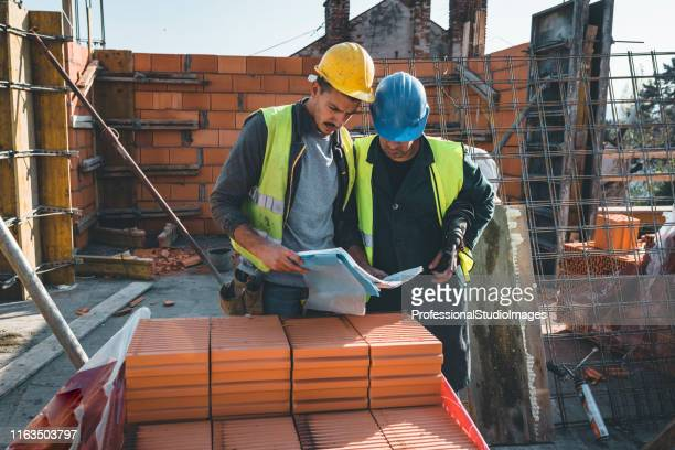 experienced construction worker is explaining building project to his coworker - hearing protection stock pictures, royalty-free photos & images