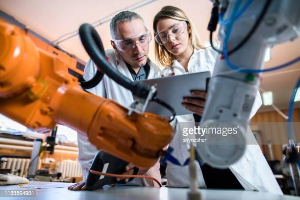 erfahrene ingenieure arbeiten bei der arbeit an maschinen im labor. - ingenieur stock-fotos und bilder