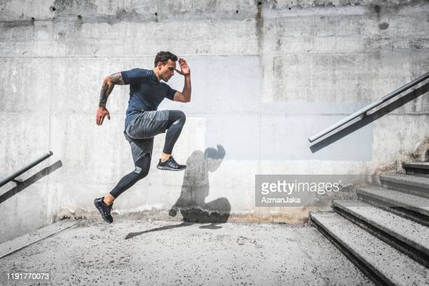 experienced male athlete running stairs with high knees - toughness stock pictures, royalty-free photos & images