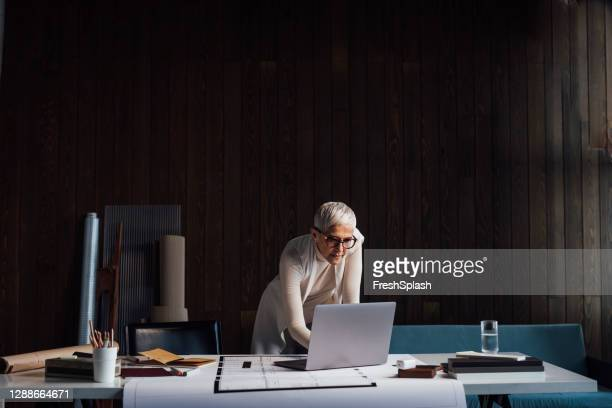 experienced mature designer working on a big new project and using her laptop pc in her home studio (dark background) - elegance stock pictures, royalty-free photos & images