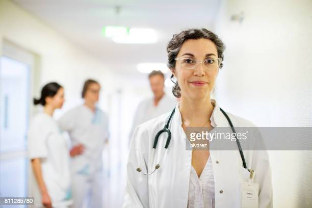 experienced mature female doctor in hospital - female doctor stock photos and pictures