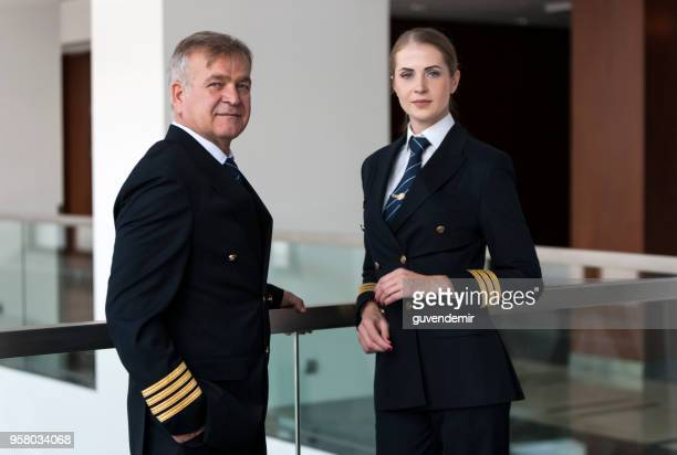 experienced senior airliner captain talking with his co-pilot before flight - team captain stock pictures, royalty-free photos & images