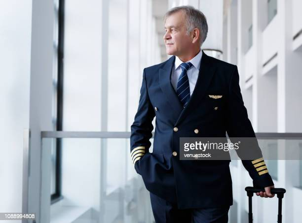 experienced senior pilot pulling his luggage in the airport terminal - pilot stock pictures, royalty-free photos & images