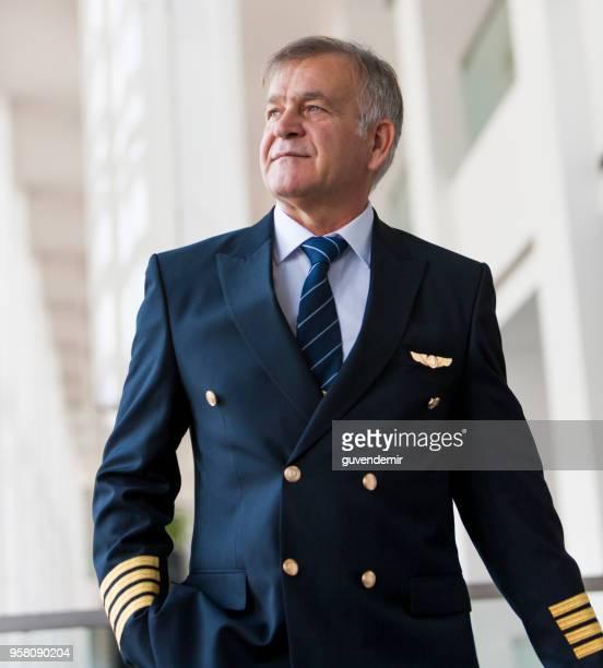 ervaren senior piloot trekken zijn bagage op de luchthaven terminal - vlieger stockfoto's en -beelden