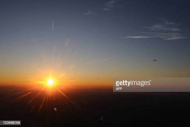 Experimental aircraft Solar Impulse with pilot Andre Borschberg onboard flies at sunrise above Payerne's Swiss airbase on July 8 2010 during the...