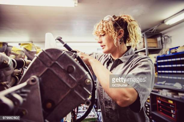 Expert female mechanic at her workshop repairing a heavy duty automobile engine