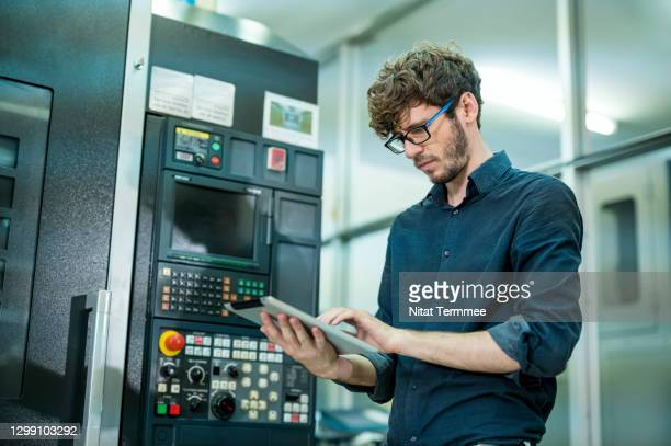 expert of male software engineer working in front of automated cnc machine. he is analyzing machine operation problems by digital tablet. - industry stock pictures, royalty-free photos & images