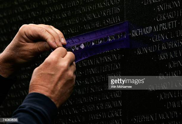 Expert stoneworker James Lee helps peels away a stencil after inscribing one of three new names on the walls of the Vietnam Veterans Memorial May 3...