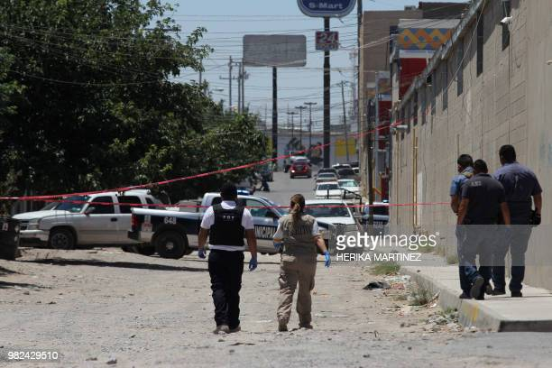 Experts and police officers work at the scene where five men and a woman were murdered in Ciudad Juarez Chihuahua state Mexico on June 23 2018 At...