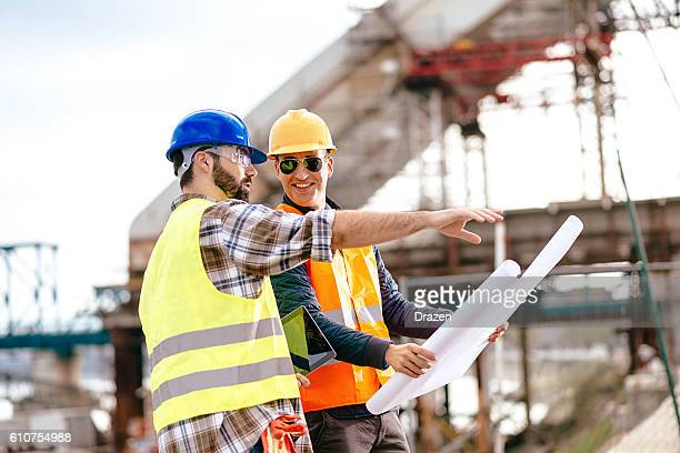 Experts having meeting on construction site and looking at blueprint