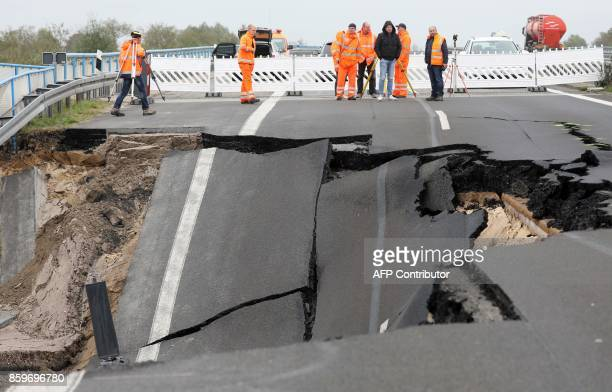 Experts inspect the cutoff section of the A20 motorway at the site of an unexplained landslide near Tribsees northern Germany on October 10 2017 The...