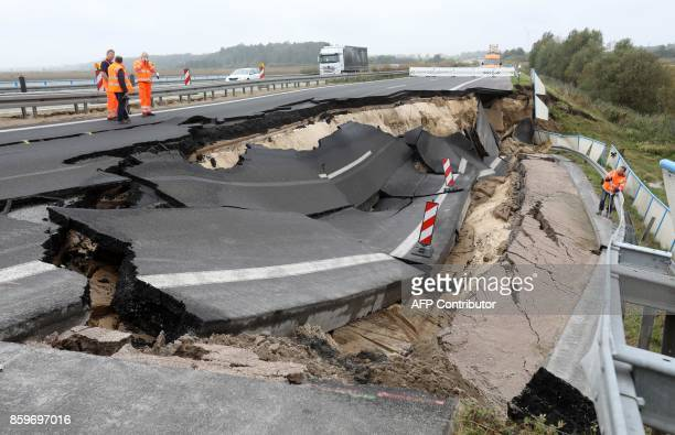 TOPSHOT Experts inspect the cutoff section of the A20 motorway at the site of an unexplained landslide near Tribsees northern Germany on October 10...