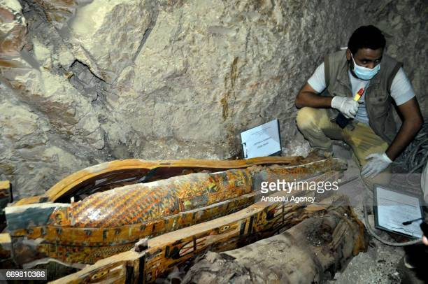 Experts inspect the sarcophagus which were found with mummies and sculptures inside a grave which is estimated about more than 3500 years old during...