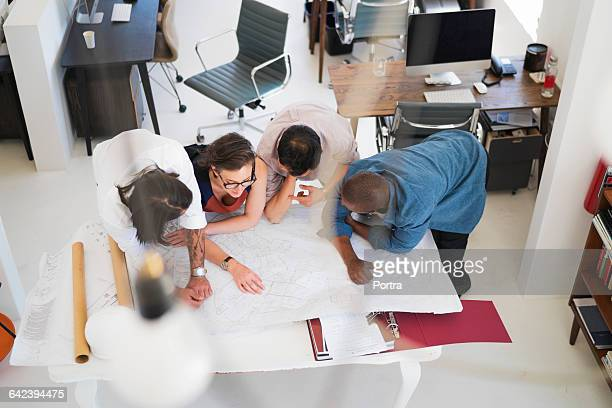 Experts leaning on blueprints in office