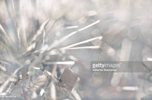 exploding silver tinsel background - tinsel stock pictures, royalty-free photos & images