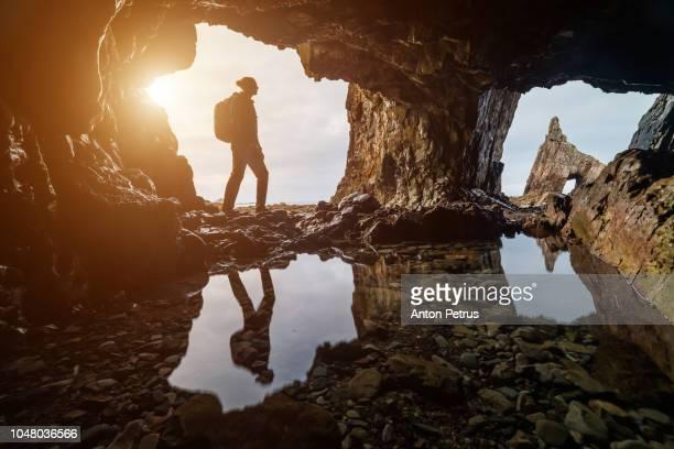 Explorer in a cave at sunset in Portizuelo beach, Asturias coast, North Spain