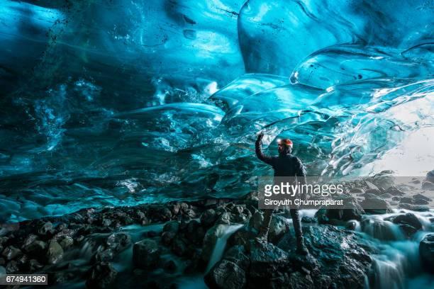 Explorer in Glacial Ice Cave, Svinafellsjokull glacier, Skaftafell National Park, Iceland