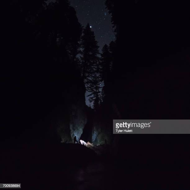 explorer in river canyon at night with headlamp under the stars - wide - spelunking stock pictures, royalty-free photos & images