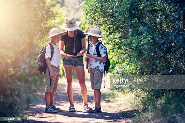 Explorer kids reading map on path