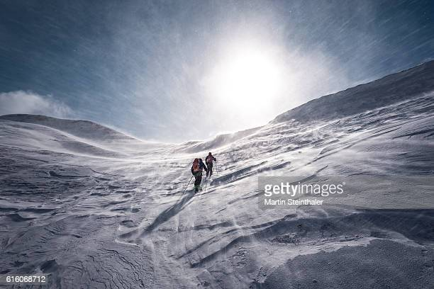 explorer on skiing tour with icy snowstorm - poolklimaat stockfoto's en -beelden