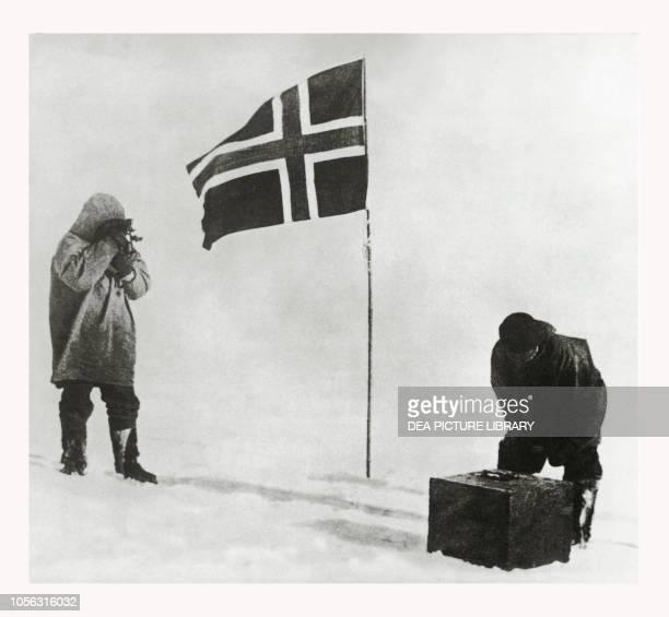 Explorer Roald Amundsen taking photos of the Norwegian flag after reaching the South Pole Antarctica 20th century