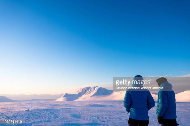 explorers look across frozen bay to snowcapped mountains at dusk - three quarter length stock pictures, royalty-free photos & images
