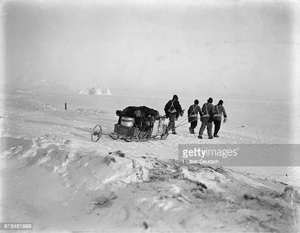 Explorers pull a sled packed with supplies across snow and ice during Robert Scott's Terra Nova Antarctic Expedition