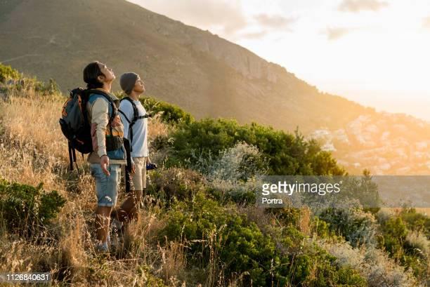 丘の上に腕を広げて立つ探検家 - 若い男性だけ ストックフォトと画像