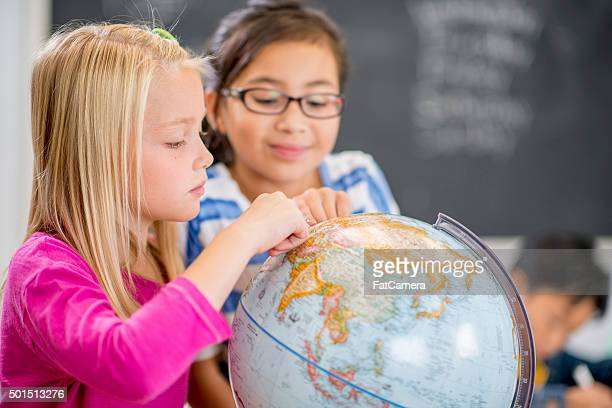 exploring a globe in geography class - aiming stock pictures, royalty-free photos & images