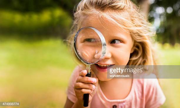 Exploring girl with magnifying glass in nature